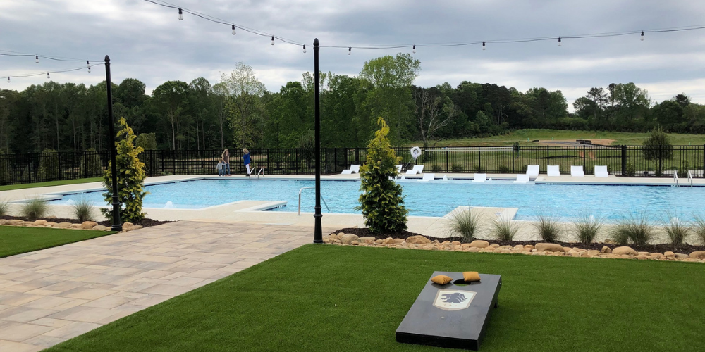 Image of pool and SR-branded cornhole board at Soft Amenity Opening at Montebello in Cumming